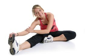 A woman preparing to exercise by stretching after her oral surgery.